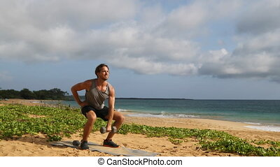 Fitness man exercising on beach doing Squat with Overhead Dumbbell Swing. Training core, legs and shoulders.