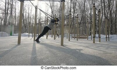 Fitness man exercising with sport straps on winter sport ground. Man bodybuilder using fitness equipment for crossfit training outdoor. Sport lifestyle