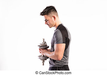 Fitness man holding dumbbell, working out, studio shot.