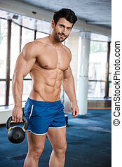 Fitness man holding kettle ball - Beautiful attractive ...