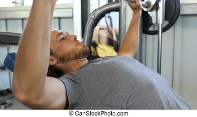 Fitness man in gym training chest muscles doing flat bench press with barbell