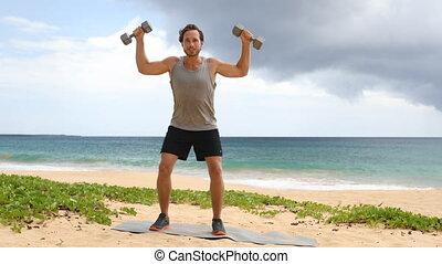 Fitness man lifting dumbbells on beach doing Shoulder ...