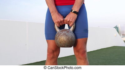 Fitness man lifting heavy kettlebell weight for legs workout.