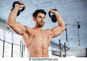 Fitness man lifting kettle ball