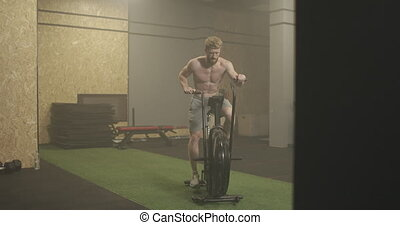 Fitness man on bicycle doing spinning at gym. Fit young male working out on gym bike. Male exercising on bicycle in health club