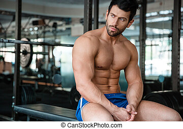 Fitness man resting on the bench in gym - Portrait of a...
