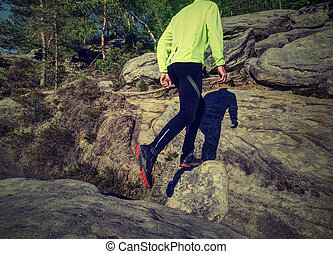 Fitness man trail runner running to rocky mountain top
