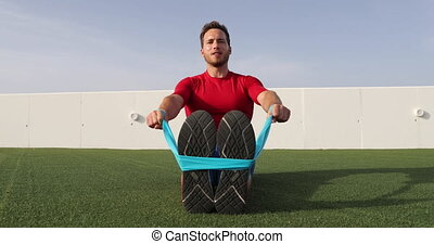 Fitness man training arms with resistance bands at outdoor gym