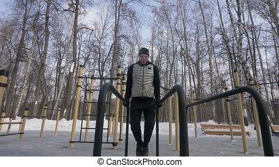 Fitness man training push ups exercise on bar on winter...