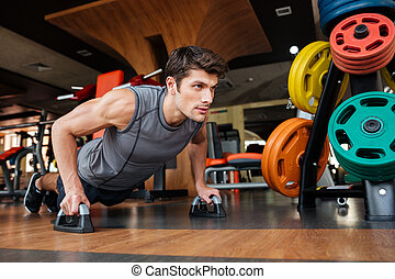 Fitness man working out and doing push-ups in gym -...