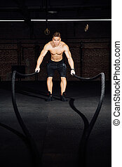 Fitness man workout with battle ropes at gym. training exercise fitted body in club. Torso.