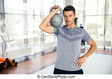Fitness man workout with kettle ball in gym