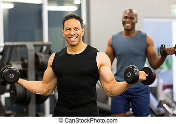 middle aged man exercising with dumbbells in gym
