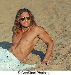 Fitness model man with long hair and wearing sunglasses posing on the beach
