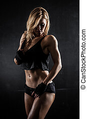 Fitness model - Smiling athletic woman showing muscles on...