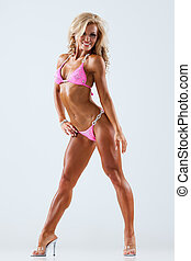 Fitness model - Smiling athletic woman in pink bikini...