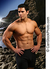Fitness model - Young male fitness model at the beach with...