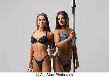 Fitness models in bikinis shot near pylon