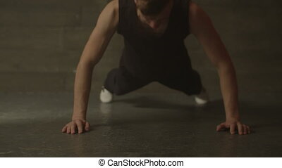 Fitness muscular man doing push-ups exercise at gym