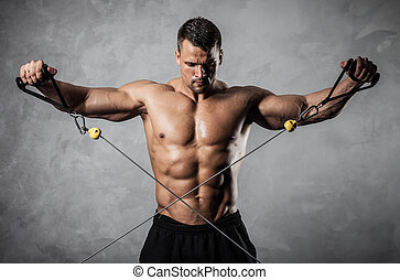 Fitness on crossover - Brutal athletic man pumping up...