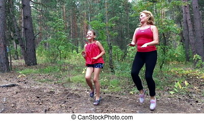 Fitness outdoors mom and daughter slow motion