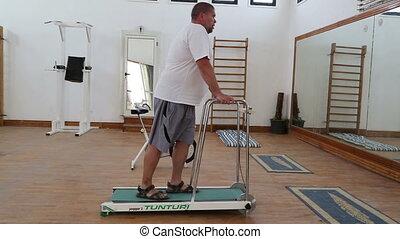 fitness - overweight man running on trainer treadmill