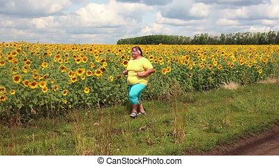 fitness - overweight woman running along field of sunflowers