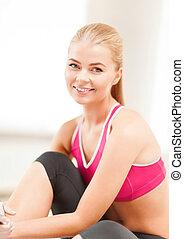 beautiful sporty woman having break in gym - fitness, people...