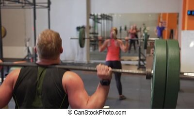 Fitness people doing back squat exercise in gym