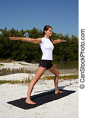 Fitness - Attractive woman on beach doing yoga poses