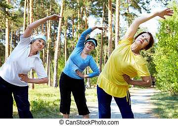 Fitness - Portrait of aged women with their arms raised...