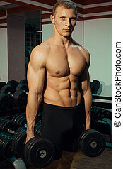 Fitness. Powerful guy with a dumbbell