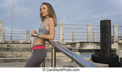 Fitness pretty blonde woman at the harbour in the morning