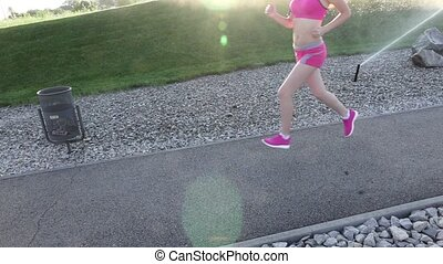 Fitness routine for women - athletic girl runner jogging along road wide angle. Slow motion
