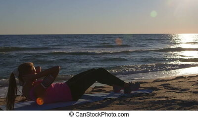 Fitness routine for women - athletic girl doing abdominal crunch on the beach