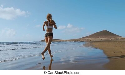 Fitness runner woman running on beach listening to music motivation with phone case sport armband strap. Sporty athlete training cardio barefoot with determination under summer sun