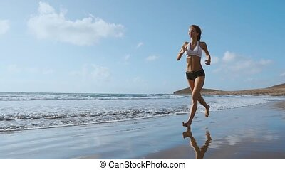 Fitness runner woman running on beach listening to music...