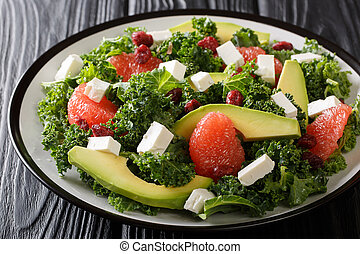 Fitness salad of kale, avocado, grapefruit, feta and dried cranberries close-up on a plate. horizontal