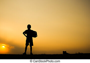 Fitness silhouette sunrise A boy holding soccer ball after play, workout wellness concept.