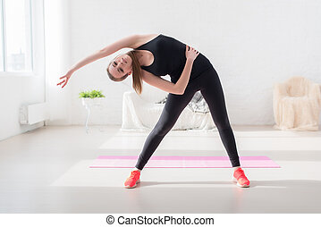 fitness slim girl doing yoga stretching exercise side body...