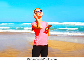 Fitness smiling woman listens to music in a wireless headphones with smartphone on the beach