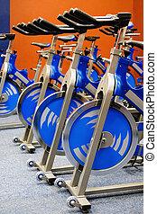 Fitness centre spinning studio, few blue bikes