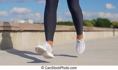 feet of young woman running outdoors - fitness, sport and ...
