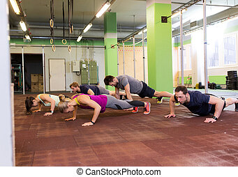 group of people doing push-ups in gym
