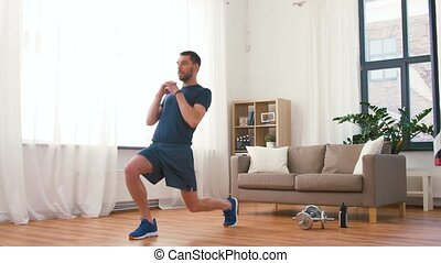 man exercising and doing lunge at home - fitness, sport and ...