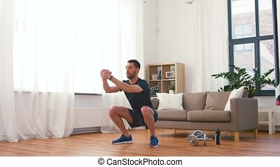 man exercising and doing squats at home - fitness, sport and...