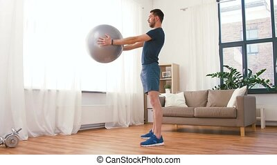 man exercising and doing squats with ball at home - fitness,...