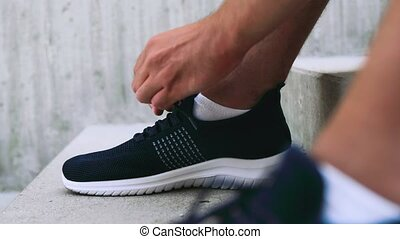fitness, sport and healthy lifestyle concept - man tying laces of his sneakers on street