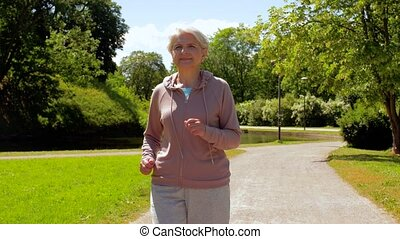 senior woman running along summer park - fitness, sport and...