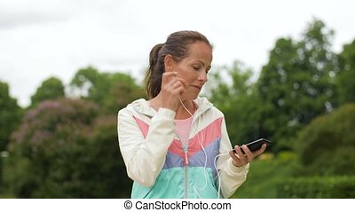 woman listening to music on smartphone at park